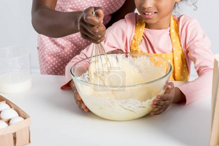 Photo pour Vue partielle des Afro-américains mère et fille, mélange de pâte avec le fouet dans la cuisine - image libre de droit