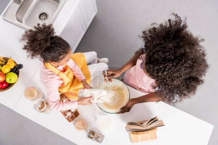 Photo for Overhead view of african american mother and curly daughter making dough in bowl on kitchen - Royalty Free Image
