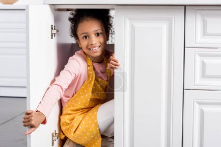 smiling african american child in apron hiding on kitchen