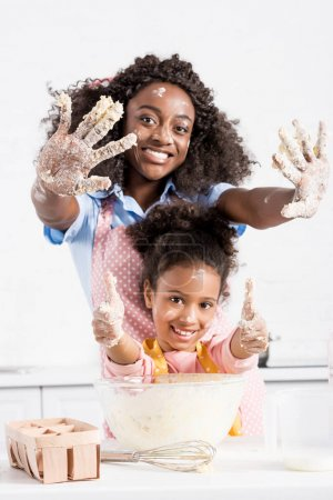 smiling african american mother and funny daughter showing hands in dough and thumbs up on kitchen
