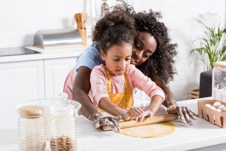 Photo pour Une mère afro-américaine et kid, rouler la pâte avec le rouleau à pâtisserie ensemble dans la cuisine - image libre de droit