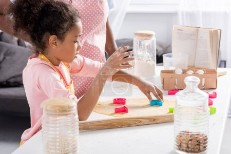 Photo for African american daughter making cookies with cookie cutters on kitchen - Royalty Free Image