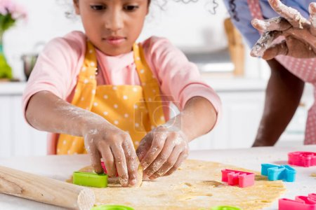 Photo for African american mother and daughter cutting cookies from raw dough on kitchen - Royalty Free Image