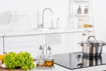 fresh ingredientes and electric stove with saucepan on kitchen
