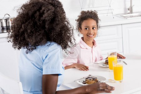 happy african american family having pancakes and orange juice for breakfast in dining room