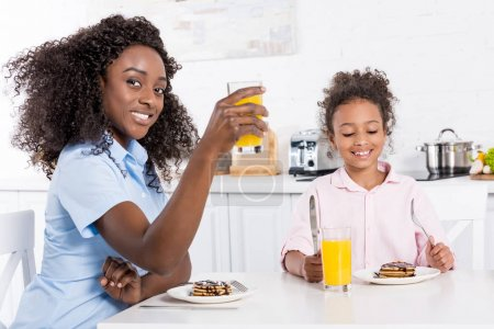 african american mother and daughter having breakfast with pancakes and orange juice in dining room