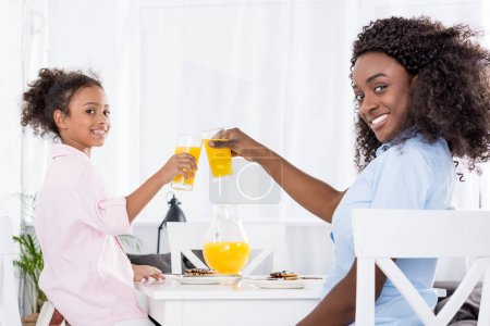 smiling african american mother and daughter clinking glasses with orange juice
