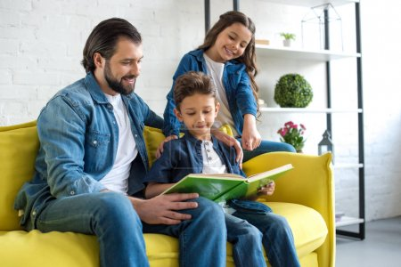 smiling father with two kids reading book together while sitting on couch at home