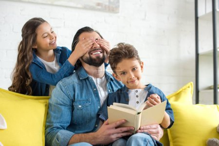 cute little daughter closing eyes to happy father while father and son reading book on sofa at home
