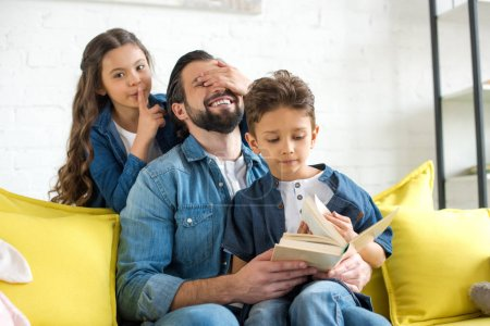 happy father with cute little children reading book together at home