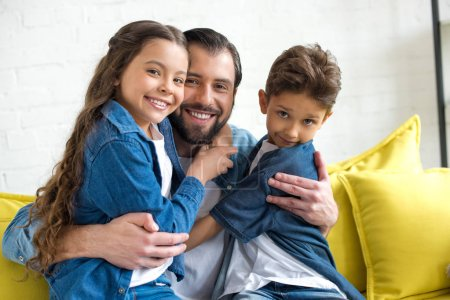 happy father hugging adorable little children and smiling at camera together at home