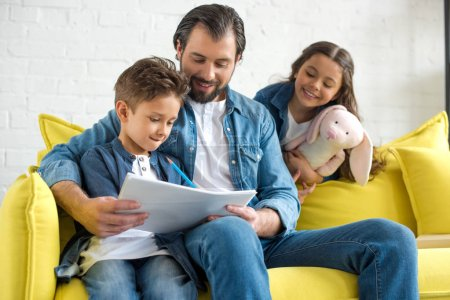 happy father with two adorable little kids spending time together at home