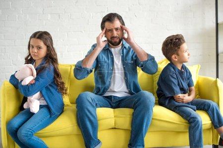 Photo pour Contrarié père avec maux de tête regarder la caméra tout en étant assis sur le canapé entre deux enfants - image libre de droit