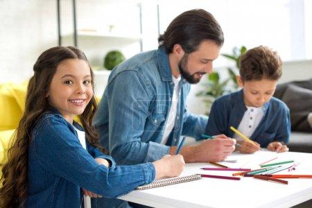 Photo pour Enfant adorable, souriant à la caméra lors du dessin avec le père et son frère à la maison - image libre de droit