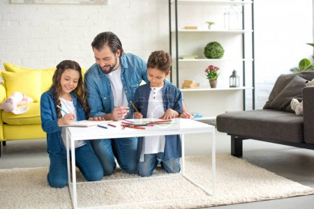 happy father with two kids kneeling on carpet and drawing with colored pencils at home