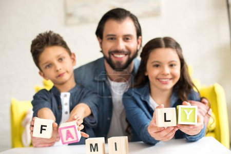 happy father with cute little children holding cubes with word family and smiling at camera