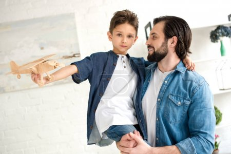 happy father carrying adorable little son playing with toy plane and looking at camera at home