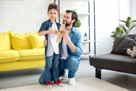 happy father and little son playing with wooden toy plane at home