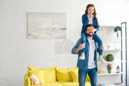 happy father carrying smiling daughter on neck and having fun together at home