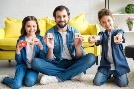 happy father and two kids holding cubes with word mother and smiling at camera