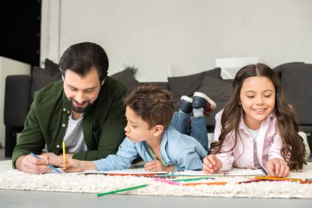 smiling father with cute kids lying on carpet and drawing with colored pencils