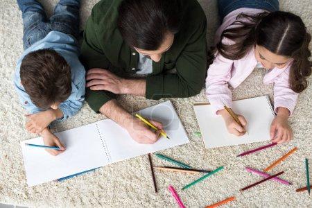 Photo pour Vue aérienne de père avec enfants dessin avec des crayons de couleur à la maison - image libre de droit
