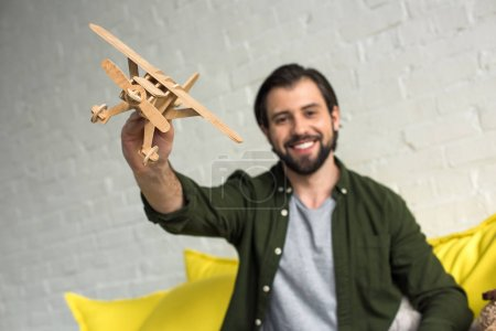 close-up view of happy young man playing with wooden toy plane and smiling at camera