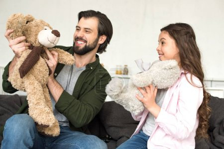 happy father and daughter playing with teddy bears at home