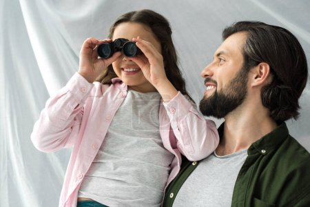 happy father looking at cute little daughter playing with binoculars