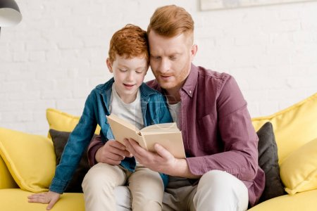 father and son sitting on sofa and reading book together