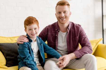 happy redhead father and son smiling at camera while sitting together on couch