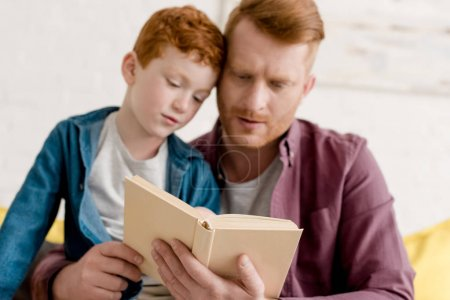 close-up view of focused father and son reading book together at home