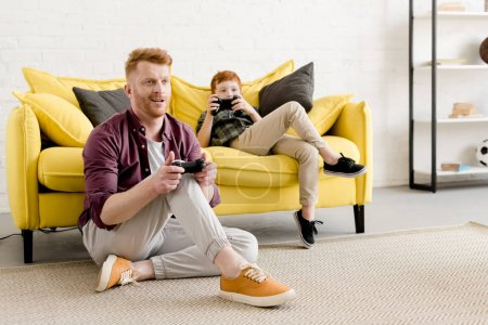 smiling red haired father and son playing with joysticks together at home