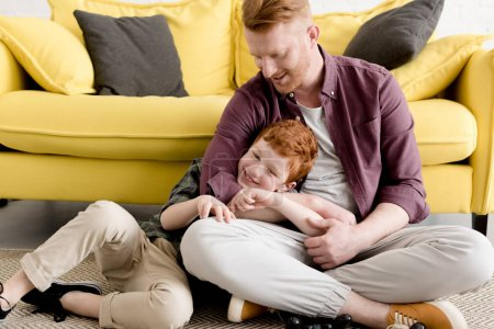 happy red haired father and son spending time together at home