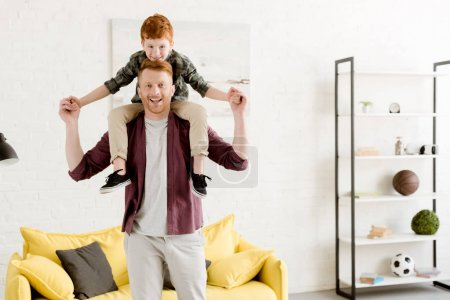 happy father carrying adorable smiling little son on neck at home