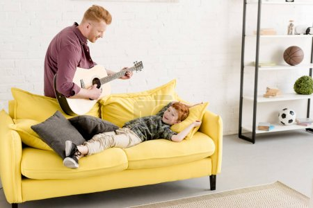 happy father playing guitar and cute smiling little son lying on couch