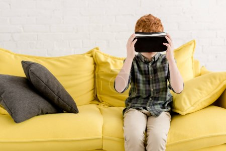 Photo for Cute little boy in virtual reality headset sitting on couch - Royalty Free Image