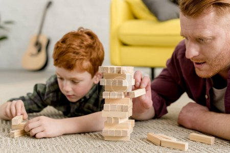 cropped shot of concentrated father and son building towers from wooden blocks at home