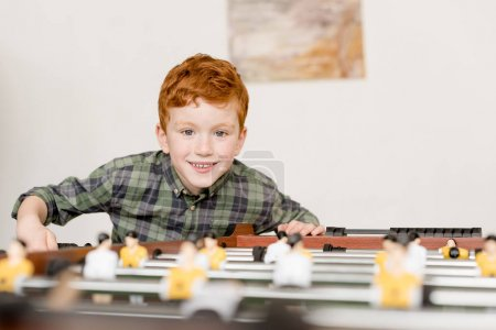 cute smiling little boy playing table football
