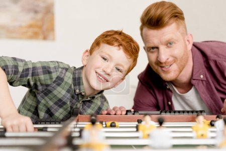 happy redhead father and son smiling at camera while playing table football together at home