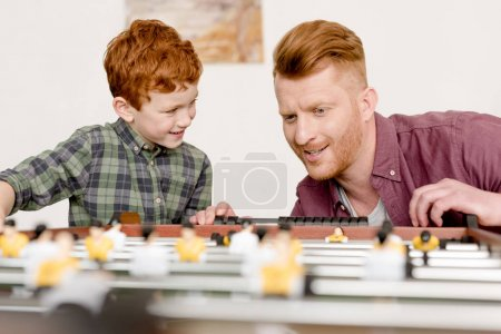 happy redhead father and son playing table football together at home
