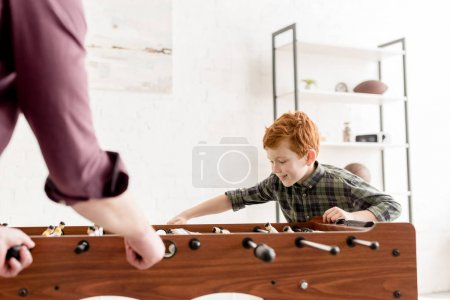 selective focus of father and cute smiling son playing table football together at home