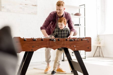 Photo for Happy redhead father and son playing table football together at home - Royalty Free Image