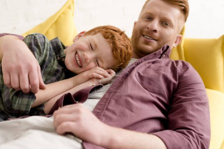 happy redhead father and son smiling and having fun together at home