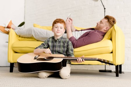 Photo for Cute little boy holding acoustic guitar ad smiling at camera while father using digital tablet on sofa behind - Royalty Free Image