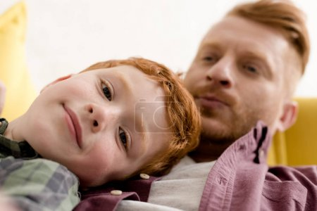 close-up view of cute little boy smiling at camera while spending time with father at home