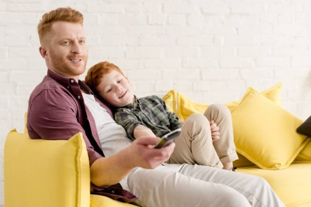 happy father and son sitting together on sofa and using remote controller while watching tv at home