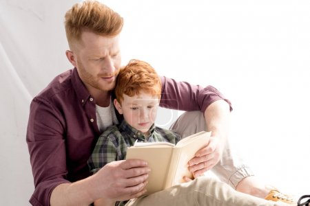 redhead father and son reading book together at home