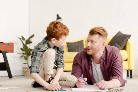 father and son looking at each other while drawing together at home