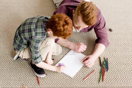 Photo pour Vue aérienne du roux père et fils, réunissant sur tapis - image libre de droit